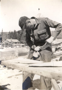 A CCC worker near Acadia National Park using a tool at a workbench.